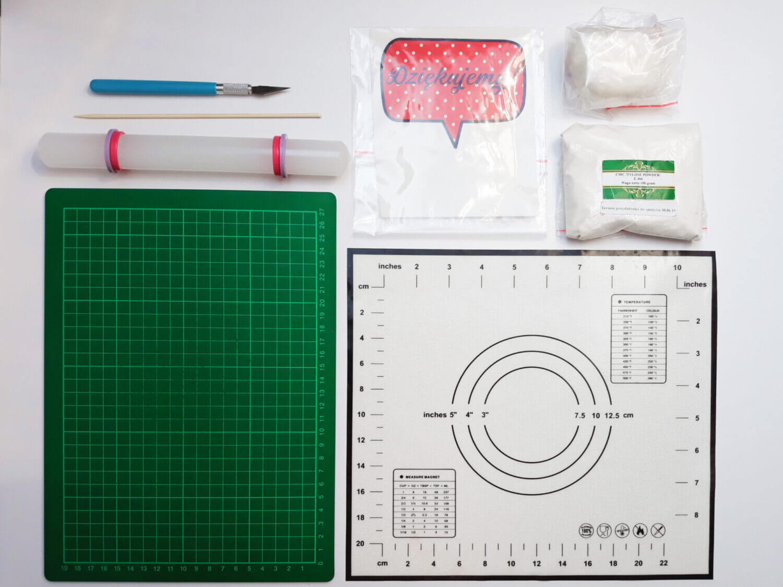 Potrzebne narzędzia do zrobienia toppera z wydrukiem cukrowym, skalpel nożyk, wydruk na masie cukrowej, masa cukrowa, cmc, patyczek, mata samogojąca mata silikonowa