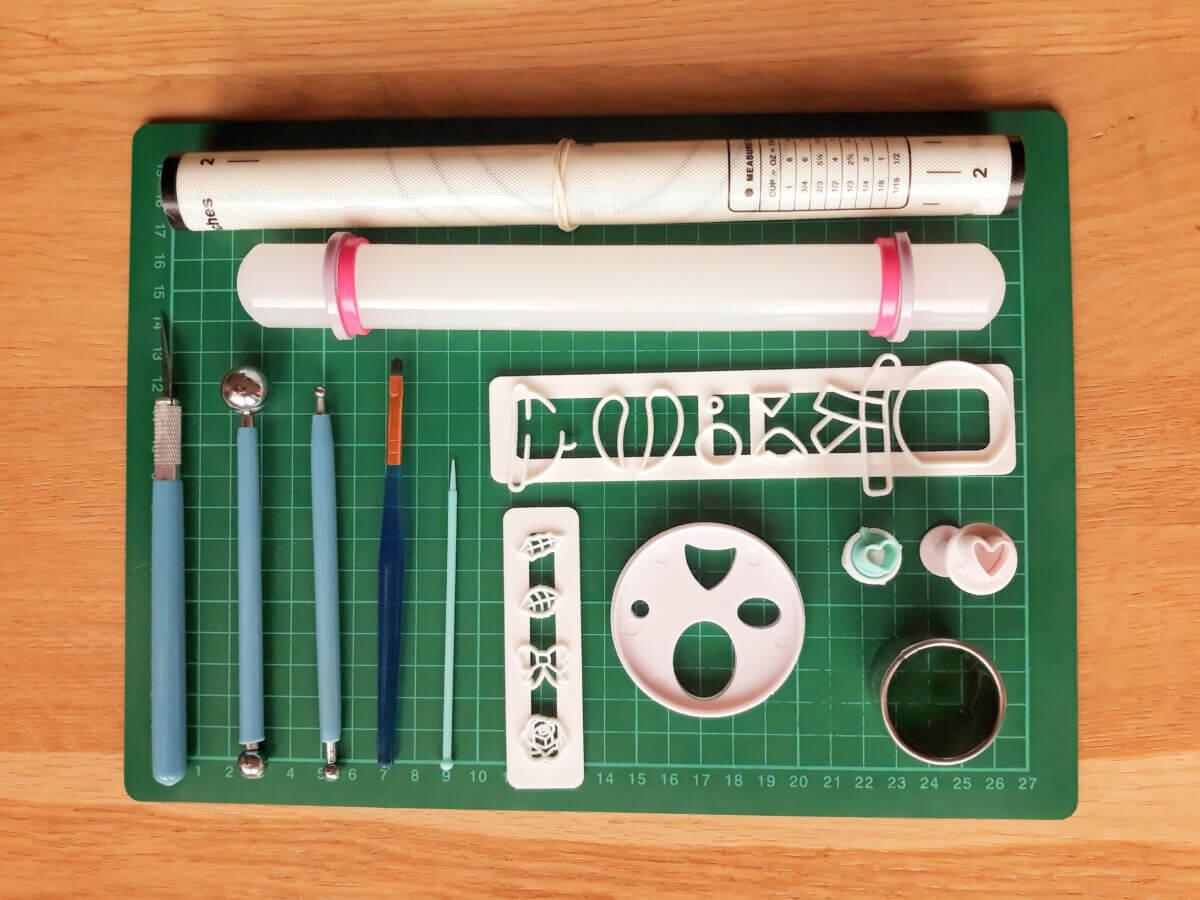 Narzędzia potrzebne do wykonania babeczki misie, potrzebne narzędzia do wykonania babeczek misiów, mata silikonowa, mata samogojąca, wykrawacze, skalpel nożyk, narzędzia kulkowe, pędzelek, wałek do masy cukrowej