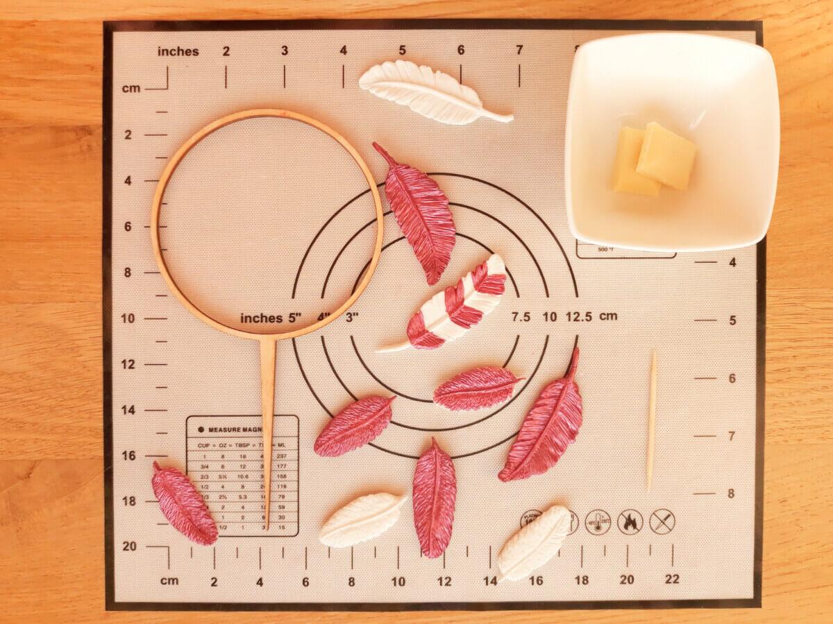przyklejanie piórek do toppera, piórka z masy cukrowej, czekolada, miseczka, okrągły topper, wykałaczka, mata silikonowa