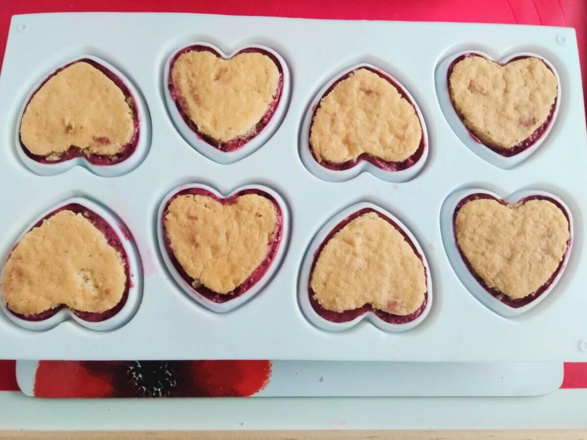 Składanie monoporcji w silikonowej formie formie w ksztalcie serc. Mus jagodowy, żelka limonkowa, biszkopt.