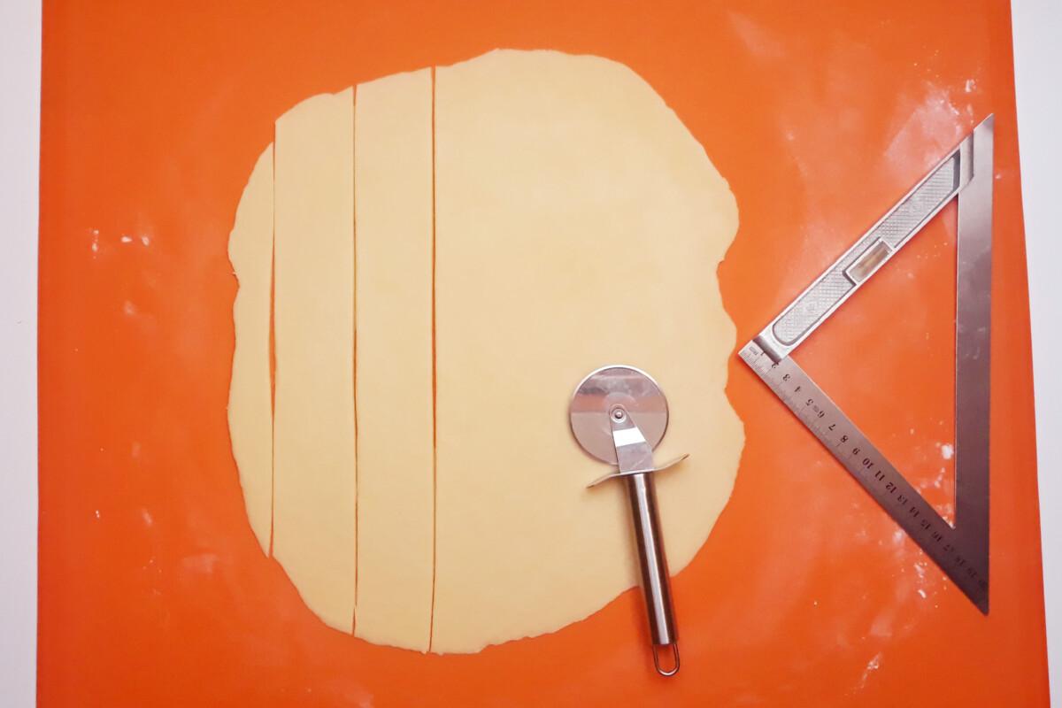 gotowe ciasto na smażone faworki rozwałkowane i pocięte, mata silikonowa nożyk, linijka