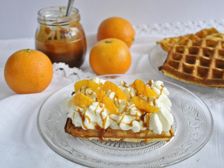 Pomarańćzowe gofry z karmelem, bitą śmietaną i pomarańczami.