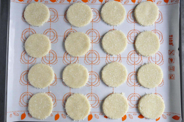 wykrojone kruche ciasteczka kokosowe, mata silikonowa, blacha z piekarnika
