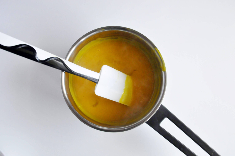 rozprowadzanie żelatyny w podgrzanej pulpie z mango i marakui, garnek, łopatka