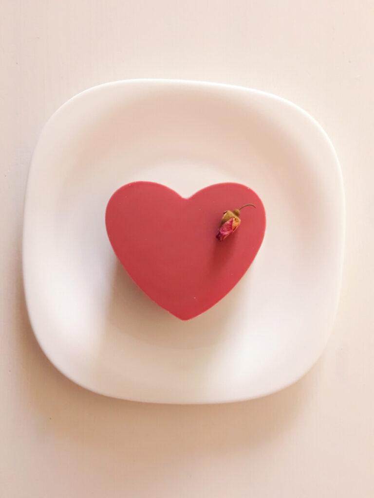 Warstwowy deser z różową czekoladą, serca z temperowanej różowej czekolady, krem chantilly z różowej czekolady, ganache z różowej czekolady, chrupka z orzechów laskowych czekolady i ryżu preparowanego, blat bezowy z orzechami włoskimi