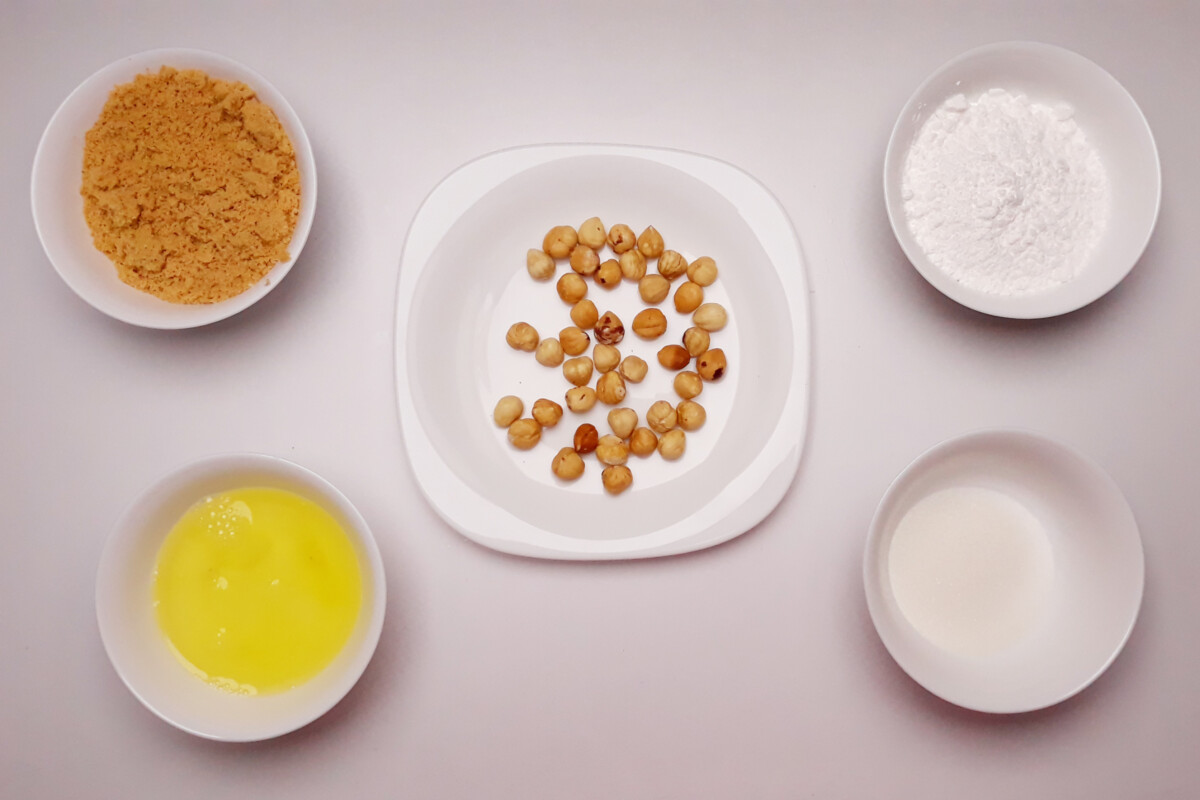 przygotowanie blatu bezowego z orzechami laskowymi mieszanie cukru pudru i mąki z orzechów laskowych miska talerz, białka, cukier puder, orzechy laskowe, mąka z orzechów laskowych, cukier