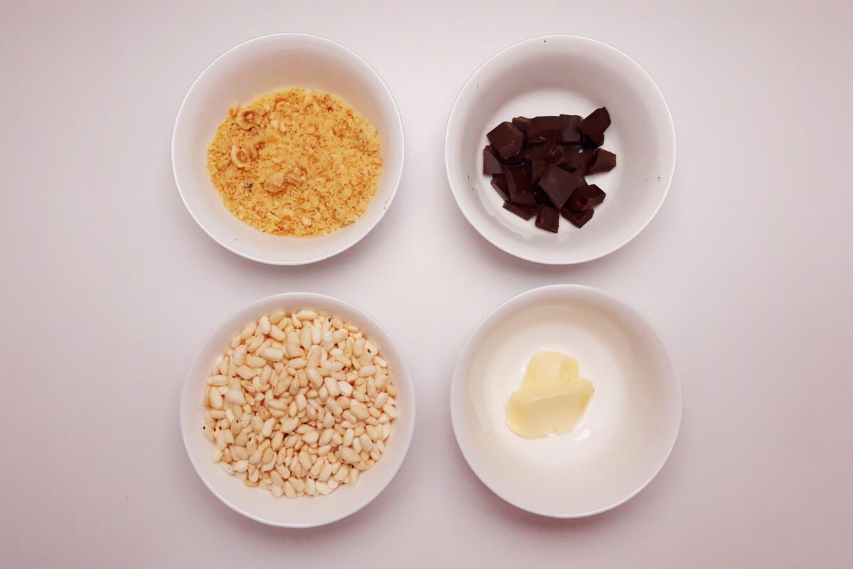 przygotowanie chrupki z orzechów, ryżu preparowanego i czekolady, miska, szpatułka, pralina z orzechów laskowych, rozpuszczona czekolada, ryż preparowany, masło, miski