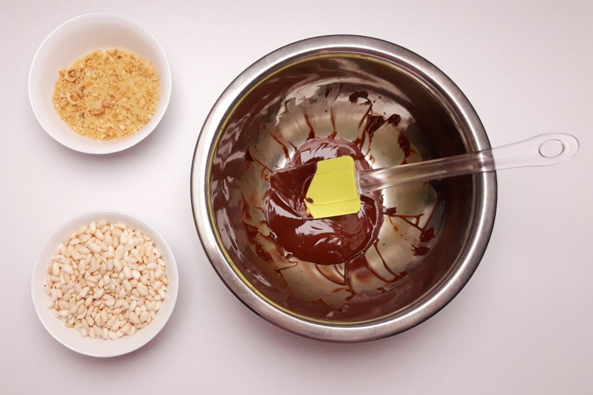 przygotowanie chrupki z orzechów, ryżu preparowanego i czekolady, miska, szpatułka, pralina z orzechów laskowych, rozpuszczona czekolada, ryż preparowany