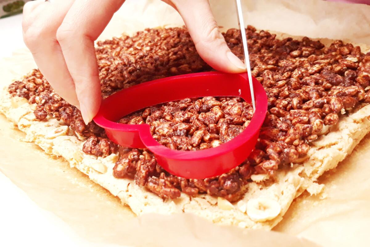 wycinanie serc z blatu bezowego, orzechów, ryżu preparowanego i czekolady, foremka w ksztłacie serca, nóż