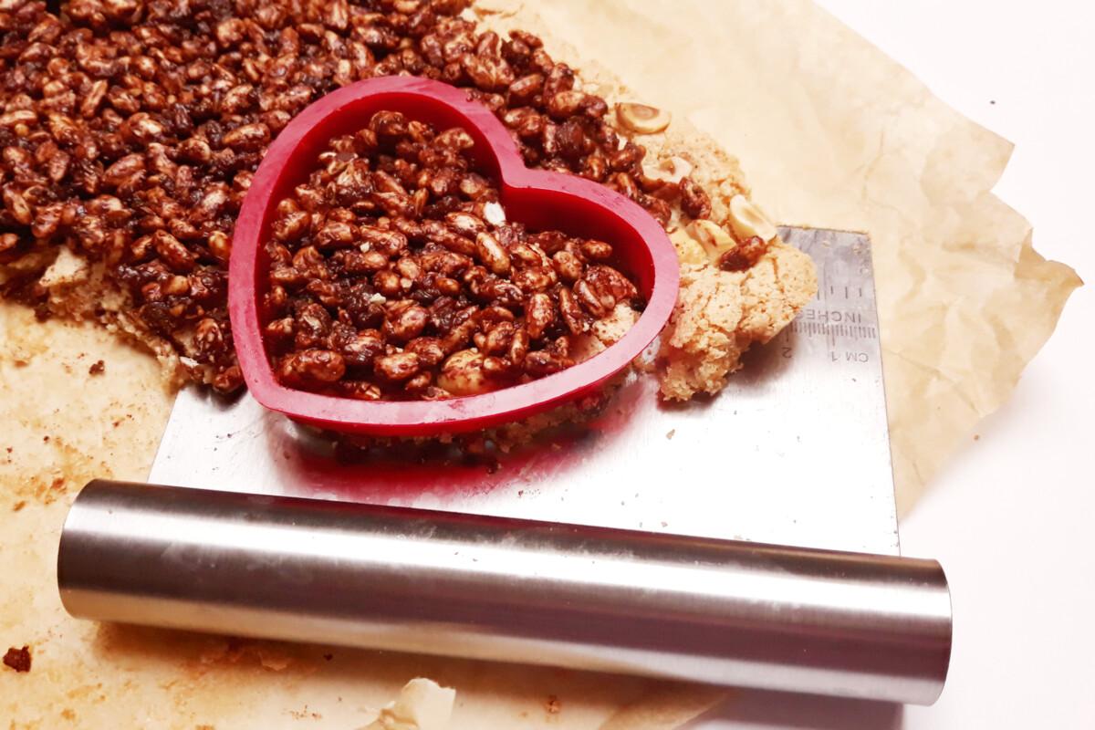 wycinanie serc z blatu bezowego, orzechów, ryżu preparowanego i czekolady, foremka w kształcie serca, packa do tortu