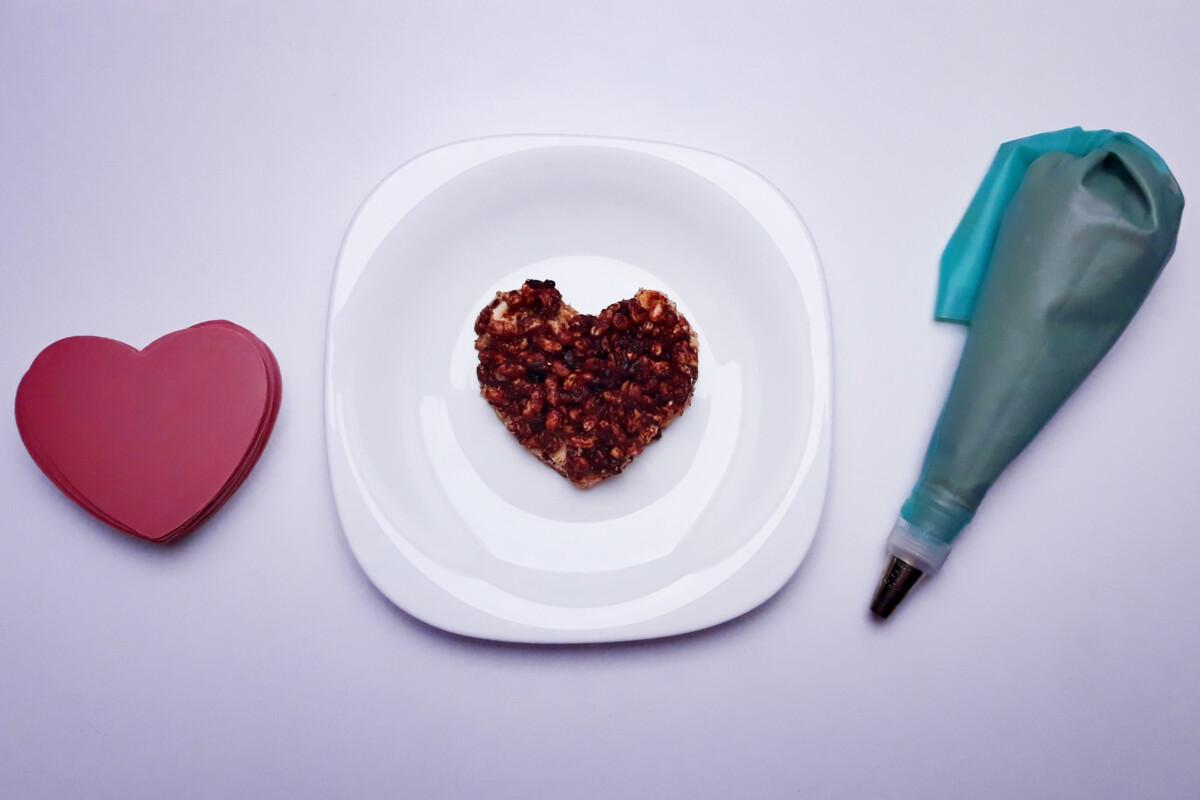 w trakcie składania deseru z różowej czekolady, blat bezowy, krucha warstwa czekoladowo-orzechowa z ryżem preparowanym, rękaw cukierniczy, serca z różowej czekolady, ganache z różowej czekolady