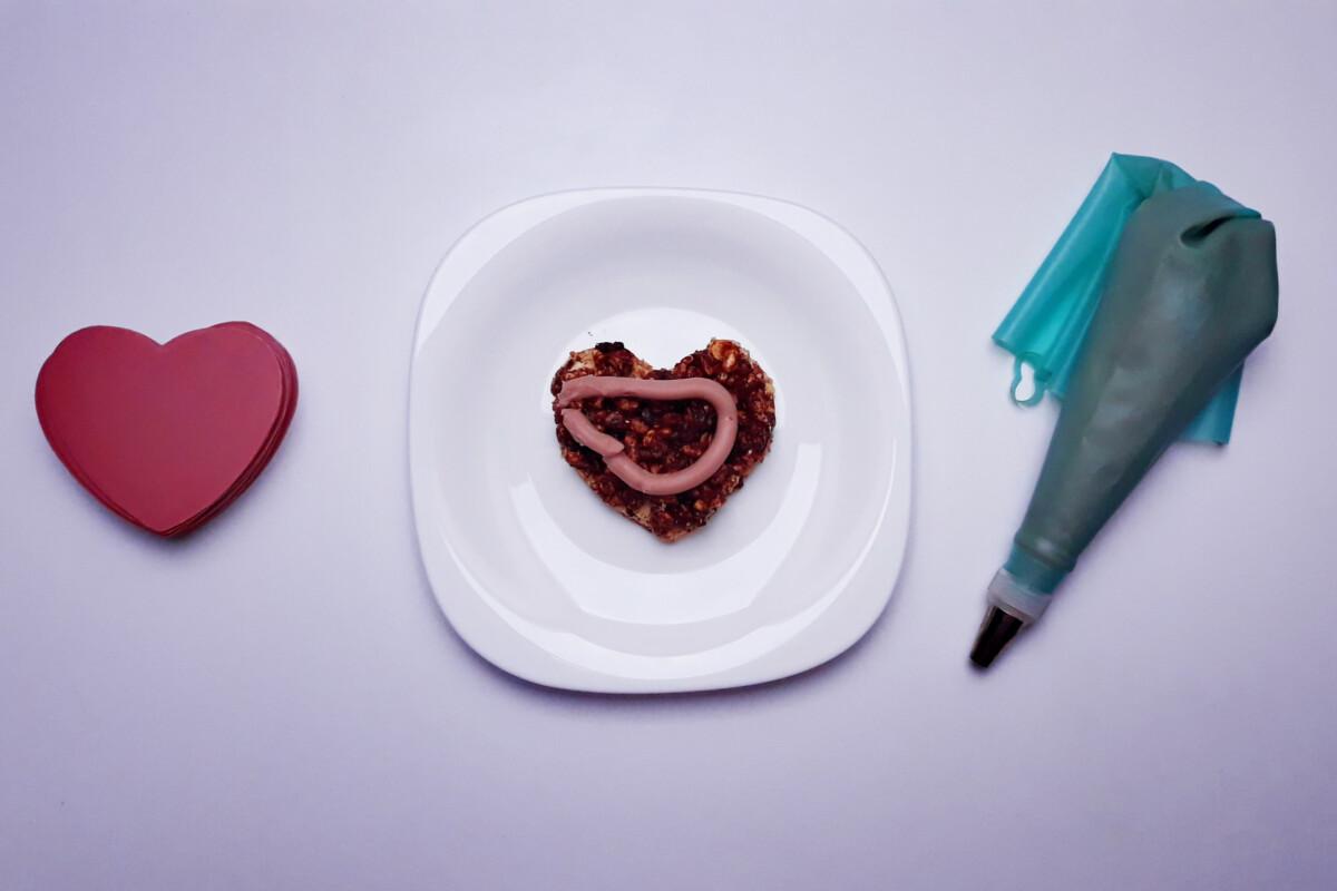 w trakcie składania deseru z różowej czekolady, blat bezowy, krucha warstwa czekoladowo-orzechowa z ryżem preparowanym