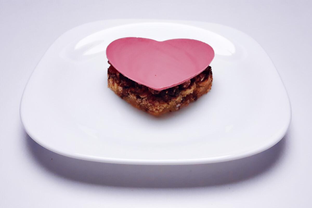 przygotowanie deseru z różowej czekolady , w trakcie składania, blat bezowy, krucha warstwa czekoladowo-orzechowa z ryżem preparowanym