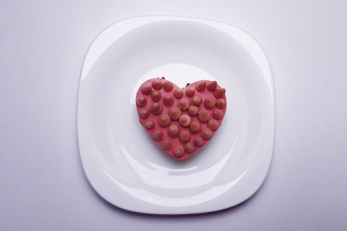ganache z różowej czekolady wyłożony za pomocą rękawa cukierniczego na serce z temperowanej różowej czekolady, talerz