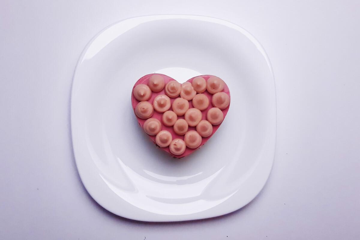 ubity ganache z różowej czekolady wyłożony za pomocą rękawa cukierniczego na serce z temperowanej różowej czekolady, talerz