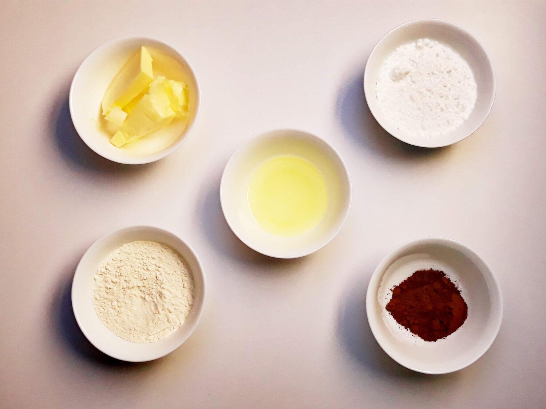 składniki na pastę ozdobną do biszkoptu joconde cake ze wzorem, kakao, masło, mąką, białko, cukier puder, miski