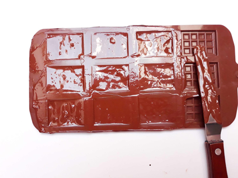 napełnianie temperowaną czekoladą formy na mini czekoladki, forma na mini czekoladki, miska, szpatułka, czekolada