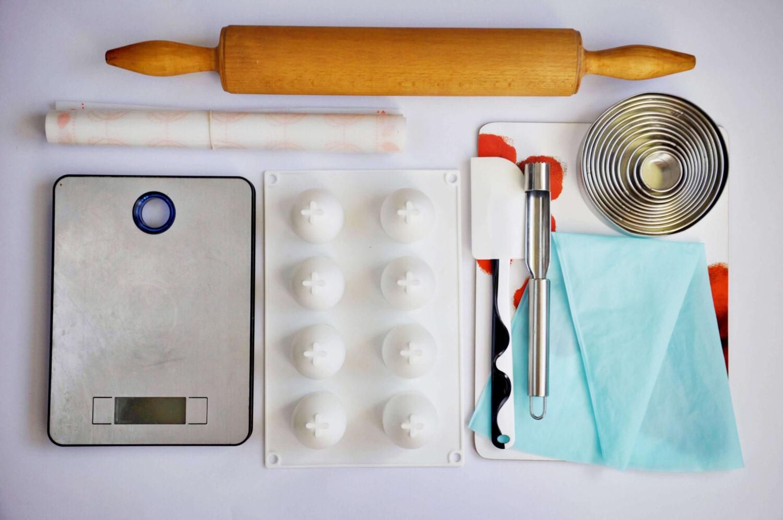 narzędzia potrzebne do wykonania monoporcji w kształcie jajek, wałek do ciasta, mata silikonowa, waga kuchenna, foremka silikonowa do monoporcji w kształcie jajek, szpatułka, wykrawacz do gniazd nasiennych, okragłe wykrawacze, podkładka, rękaw silikonowy