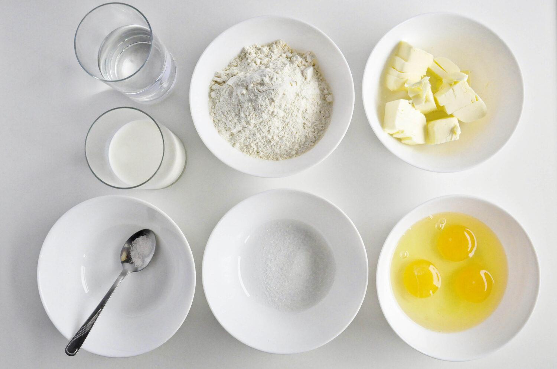 Składniki potrzebne do przygotowania ciasta parzonego na ptysie: woda, mleko, masło, mąka pszenna, jaja, cukier, szczypta soli