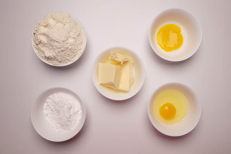 składniki na kruche ciasto do tartaletek, jajko, żółtko, mąka, cukier puder, masło