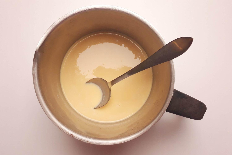 mleko wymieszane z ajerkoniankiem, garnek, łyżka