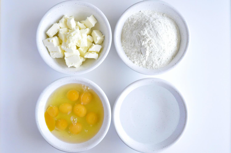 składniki potrzebne do przygotowania ciasta parzonego na profiterole: masło, mąka pszenna, jaja, woda