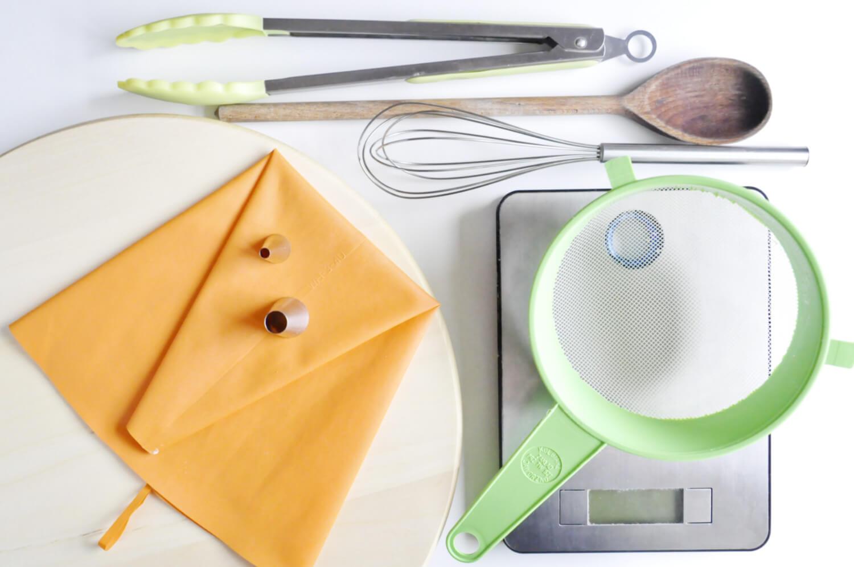 narzędzia potrzebne do przygotowania croquembouche czyli wieża z ptysi: rękaw cukierniczy, tylka z okrągłą końcówką, tylka do nadziewania, szczypce, drewniana łyżka, rózga kuchenna, waga kuchenna, sitko