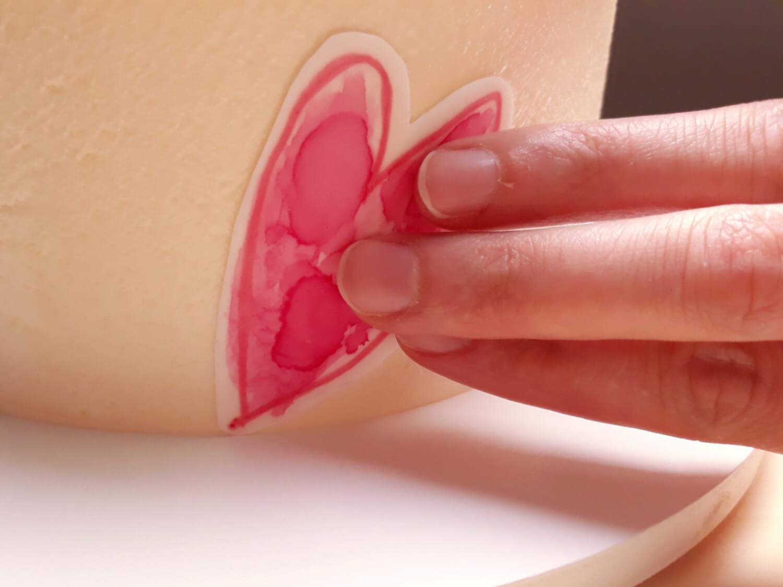 tort z sercami malowanymi na papierze cukrowym na dzień matki, niech twoje dziecko ozdobi tort, pozwól swojemu dziecku ozdobić tort, przyklejanie serc z papieru cukrowego do tortu