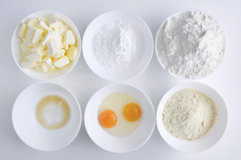 Składniki na kruche ciasto: mąka pszenna, mąka migdałowa, cukeir puder, jajko, żółtko, masło, ekstrat z wanilii
