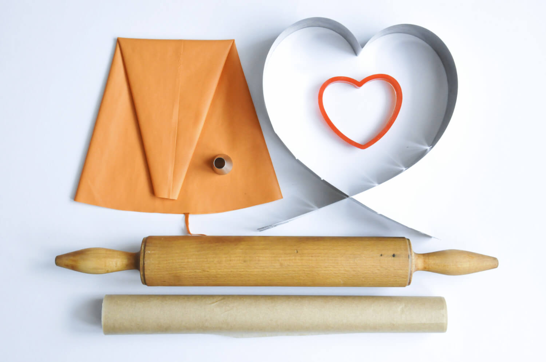 Narzędzia potrzebne do przygotowania number cake: regulowana forma w kształcie serca, wykrawacz w kształcie serca, silikonowy rękaw cukierniczy, tylka z okrągłą końcówką, wałek do ciasta, papier do pieczenia