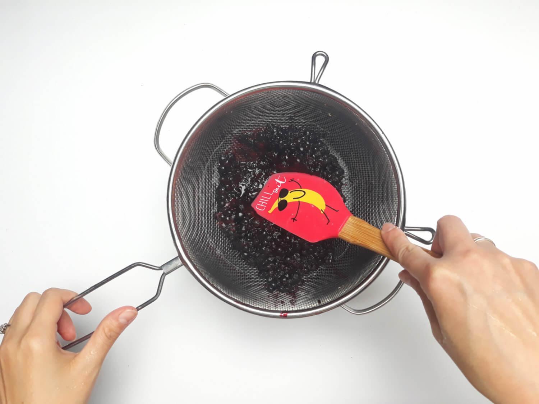 przygotowanie musu jagodowego do mini serniczków, przecieranie ugotowanych jagód przez sitko