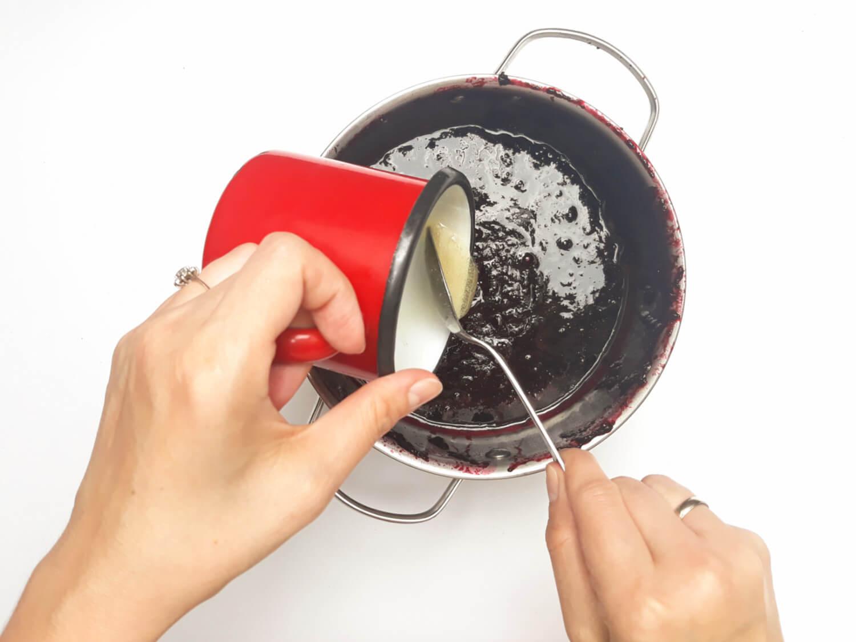przygotowanie musu jagodowego do mini serniczków, dodawanie rozpuszczonej żelatyny do przetartych jagód