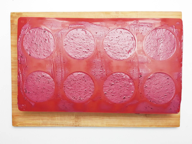 przygotowanie musu jagodowego do mini serniczków, foremka silikonowa wypełniona serniczkami z musem jagodowym