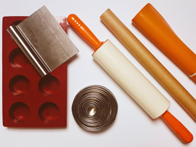 narzędza do przygotowania mini serniczków z musem jagodowym i domowymi herbatnikami, forma silikonowa, skrobka metalowa, wykrawacz metalowy okrągły, wałek silikonowo, stolnica silikonowa, papier do pieczenia