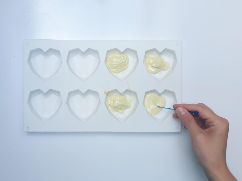 przygotowanie monoporcji w temperowanej czekoladzie, wypełnianie temperowaną białą czekoladą formy silikonowej w kształcie geometrycznych serc , wykałaczka