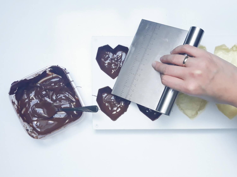 przygotowanie monoporcji w temperowanej czekoladzie, wypełnianie temperowaną białą czekoladą formy silikonowej w kształcie geometrycznych serc, wyrównywanie brzegów packą
