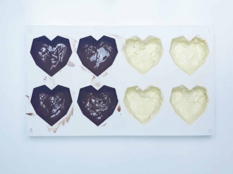 przygotowanie monoporcji w temperowanej czekoladzie, wypełnianie temperowaną białą czekoladą formy silikonowej w kształcie geometrycznych serc