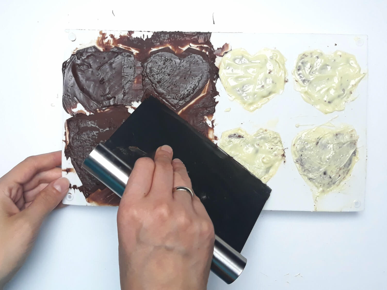 przygotowanie monoporcji w temperowanej czekoladzie, zamykanie deserków temperowaną czekoladą, zeskrobanie niepotrzebnej czekolady metalową packą