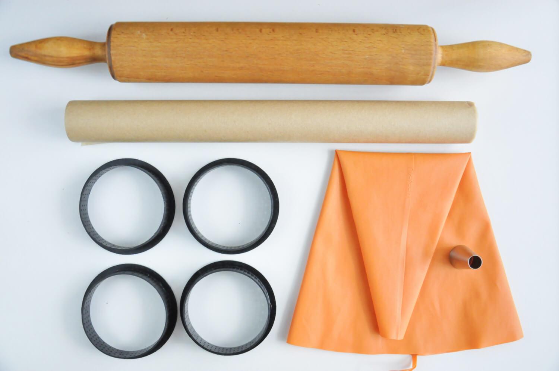 narzędzia potrzebne do przygotowania tarataletek: wałek do ciasta, papier do pieczenia, rękaw cukierniczy, tylka z okrągłą końcówką, perforowane obręcze do mini tart