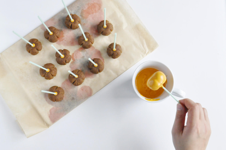 Dyniowe cake pops - zanurzanie w polewie czekoladowej.
