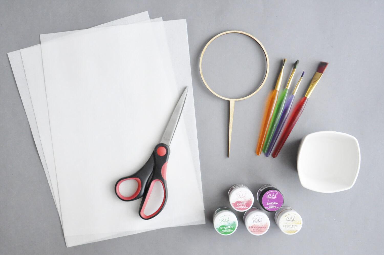 Narzędzia potrzebne do zrobienia topperu z ozdobami z papieru waflowego: papier waflowy, nożyczki, drewniany dopper, pędzelki, barwniki w proszku, miseczka z wodą