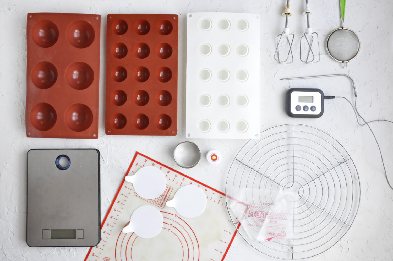 czapki Mikołaja - potrzebne narzędzia: forma silikonowa na duże półkule, forma silikonowa na małe pólkule, forma silikonowa na kulki, waga kuchenna, mata silikonowa, plastikowe podkładki na monoporcje, okrągły wykrawacz, czerwony barwnik spożywczy w żelu, rękaw cukeirniczy, kratka do studzenia, mikser, sitko, termometr cukierniczy