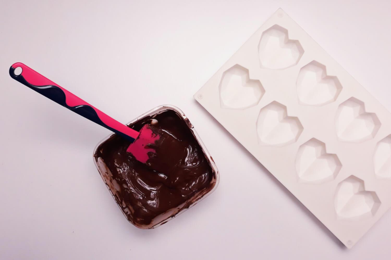 Świąteczne desery renifery piernikowe - monoporcje bożonarodzeniowe, wypełnianie foremek silikonowoych temperowaną czekoladą, czekolada, miska, formasilikonowa w kształcie diamentowych serc, łopatka silikonowa