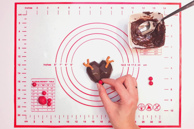 Świąteczne desery renifery piernikowe - monoporcje bożonarodzeniowe, przyklejanie nosa renifera z czekolady plastycznej