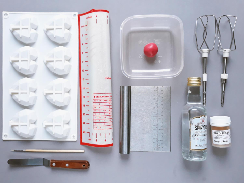 narzędzia potrzebne do wykonania deserów, forma silikonowa diamentowe serca, mata silikonowa, skrobka metalowa, szpatułka cukiernicza, pędzelek, spirytus, czekolada plastyczna, miska, trzepaczki do miksera, barwnik spożywczy w proszku
