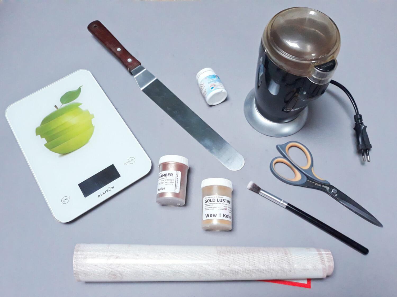 narzędzia potrzebne do przygotowania jadalnego brokatu, waga kuchenna, szpatuła cukiernicza, barwnik spożywczy błyszczący, klej jadalny, młynek do kawy, mata silikonow, nożyczki, pędzelek