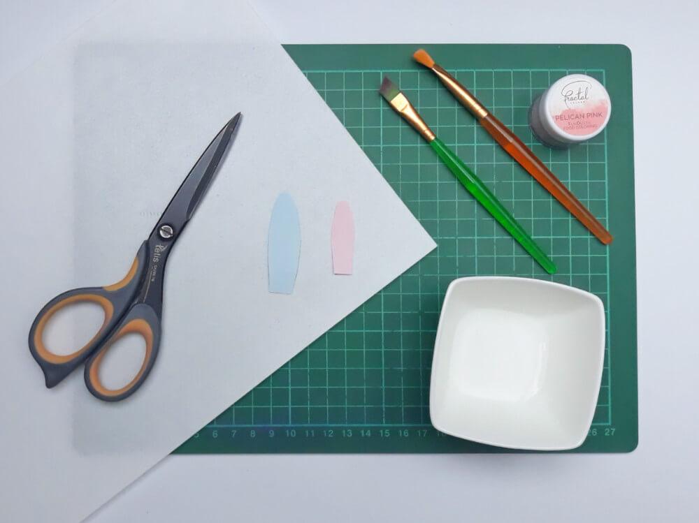 przygotowanie uszu zajączka z papieru waflowego, papier waflowy, nożyczki, miseczka z wodą, pędzelki, mata, barwnik spożywczy