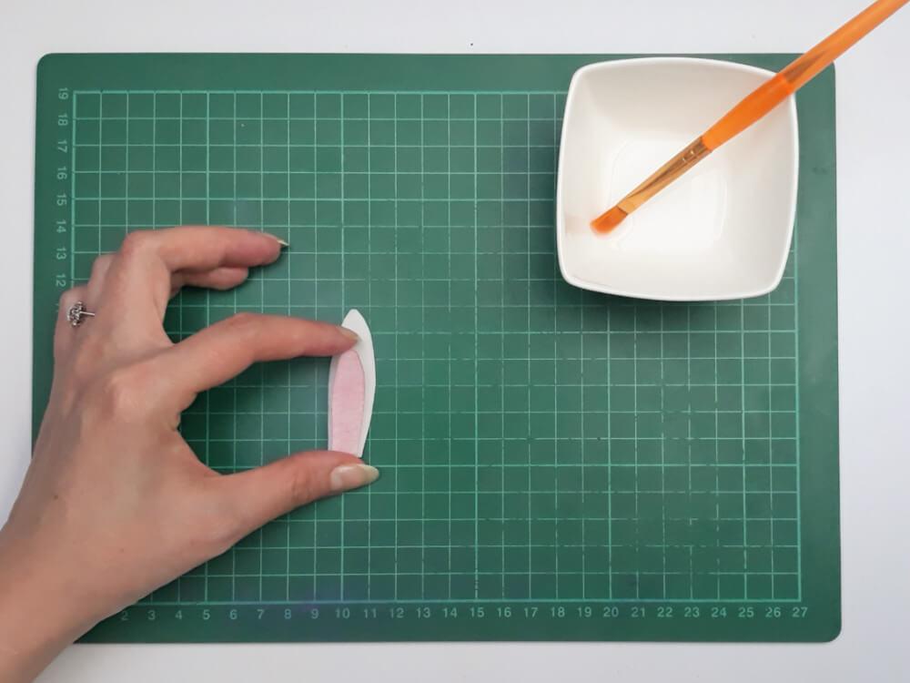 przygotowanie uszu zajączka z papieru waflowego, sklejanie elemntów, woda, pędzelek