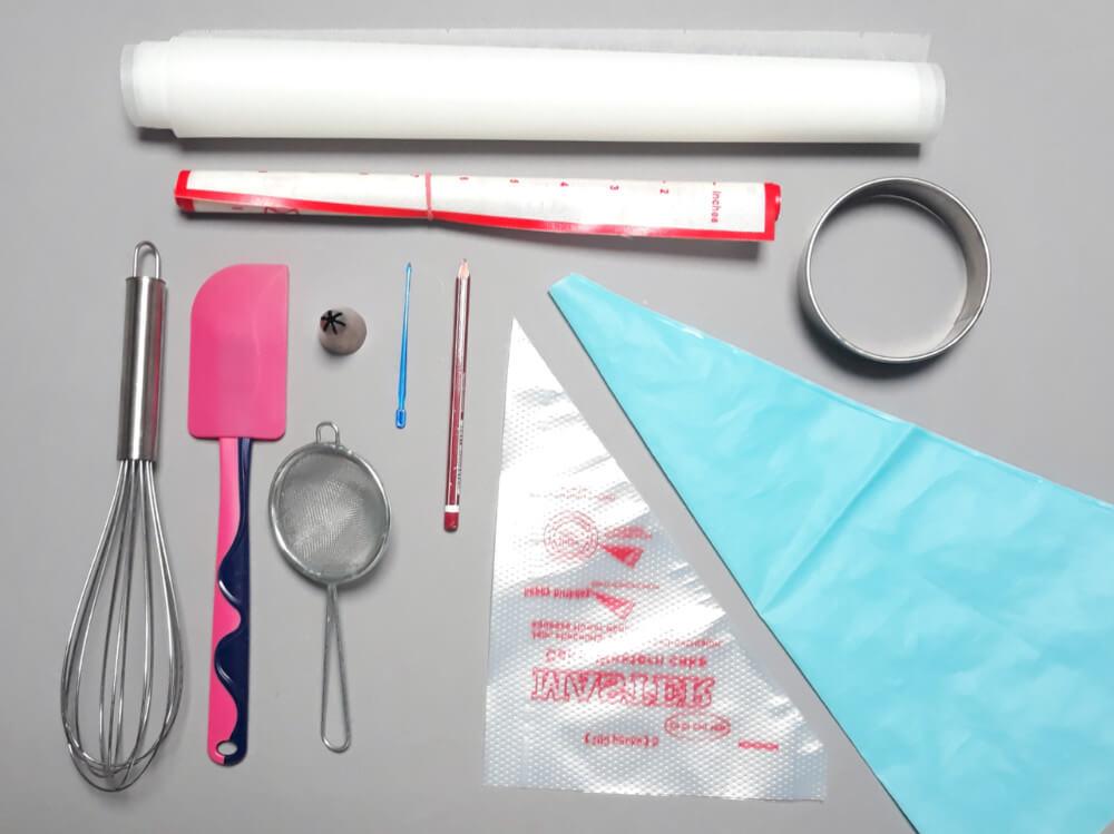narzedzia potrzebne do przygotowania biskwitów misiów: mata silikonowa, papier do pieczenia, rękaw cukierniczy, wykrawacz okrągły, sitko, wykałaczka, tylka cukiernicza, ołówek, łopatka silikonowa, trzepaczka