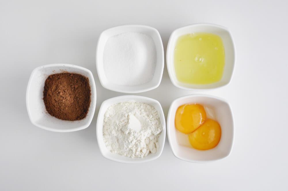 składniki na biszkopt kakaowy: jajka (białka i żółtka oddzielnie), cukier, mąka pszenna, kakao